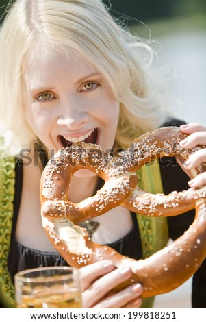 Germany, Bavaria, Munich, English Garden, Young woman eating soft pretzel, close-up