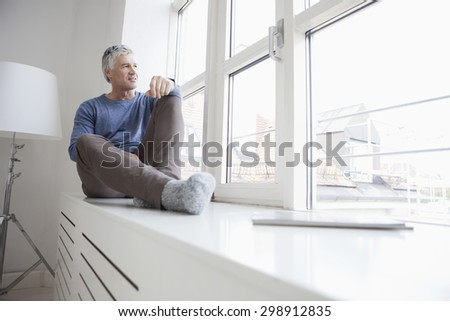 Germany, Bavaria, Munich, Portrait of mature man sitting at window, looking away
