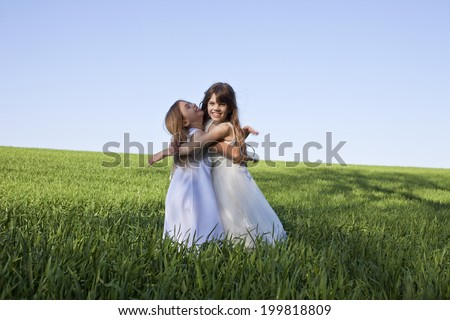 Germany, Bavaria, Two girls embracing on field, smiling, portrait - stock photo