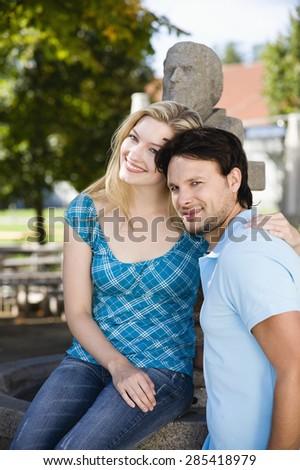 Germany, Bavaria, Upper Bavaria, Young couple embracing, smiling, portrait - stock photo