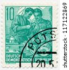 GERMANY - CIRCA 1953: A stamp printed in Germany, shows Two workers at the lathe, series Five year plan, circa 1953 - stock photo