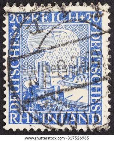 GERMANY - CIRCA 1925: a stamp printed in the Germany shows German Eagle Watching Rhine Valley, 1000 Years Union of the Rhineland with Germany, circa 1925 - stock photo