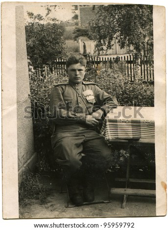 GERMANY - CIRCA 1947: Captain of the Red Army who was awarded the Order of Glory, and three medals sitting in the yard beside the table, Potsdam, Germany, circa June 7, 1945 - stock photo