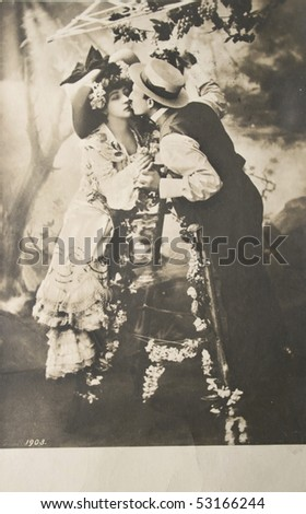 GERMANY-CIRCA 1903: Loving couple kissing in black and white. Hand-tinted photograph postcard,circa 1903
