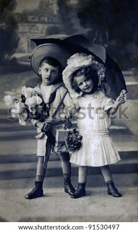 GERMANY - CIRCA 1909: Postcard printed in the Germany shows boy and girl under an umbrella, circa 1909 - stock photo