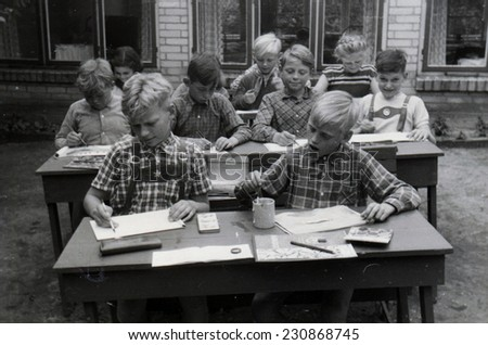 GERMANY - CIRCA 1950s: A group of schoolboys in traditional Bavarian shorts sitting at their desks during lesson, passing in the school yard. Germany, 1950s. Reproduction of an antique photo. - stock photo