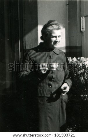 GERMANY - CIRCA 1960s: An antique photo of elderly woman with a cup of tea in hand standing near the front door of a private house