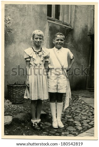 GERMANY - CIRCA 1930s: An antique photo of girl and boy in white dresses on the background of house
