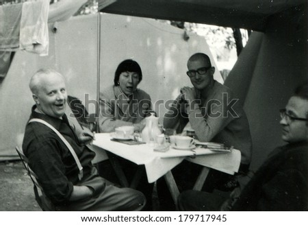 GERMANY - CIRCA 1950s: An antique photo of group of people drinking tea at a folding table in the campsite