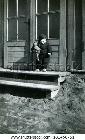 GERMANY - CIRCA 1950s: An antique photo of little boy with a teddy bear in the hands of the steps of a private house