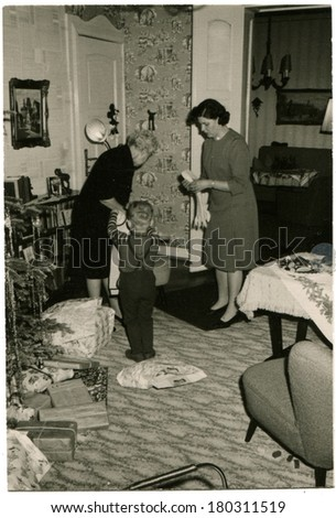 GERMANY - CIRCA 1950s: An antique photo of Two women, a mother and grandmother, and a little boy getting ready for Christmas