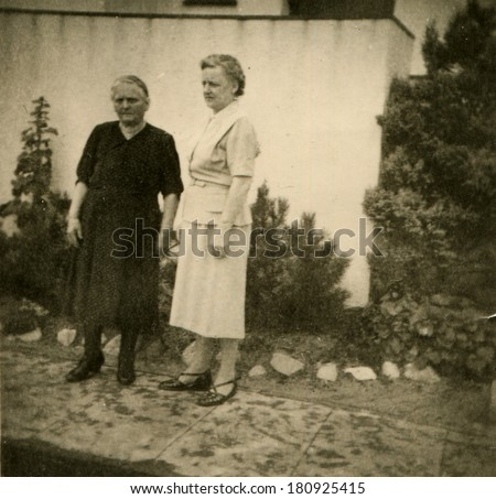GERMANY - CIRCA 1950s: An antique photo of two women posing near a private house