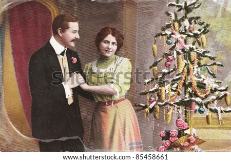 GERMANY- CIRCA 1910: Vintage christmas card with weathered edges printed in Germany in 1915 with loving couple beside a christmas tree  , circa 1910. - stock photo