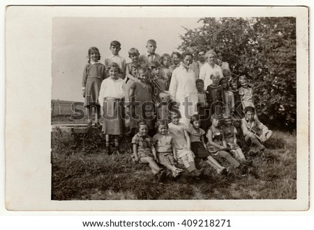 GERMANY - CIRCA 1934: Vintage photo shows group of children with female doctors.