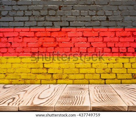 Germany flag painted on brick wall with wooden floor - stock photo