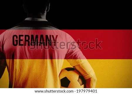 Germany football player holding ball against germany national flag - stock photo