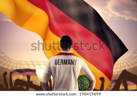 Germany football player holding ball against large football stadium under bright blue sky - stock photo