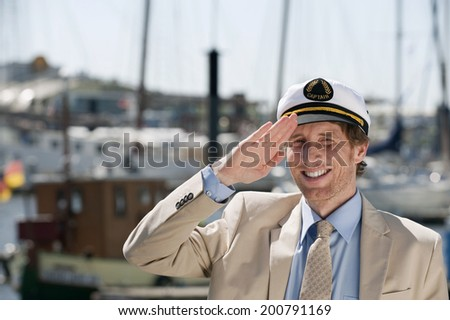 Germany Hamburg man saluting in sailor cap smiling harbor with boats in background - stock photo