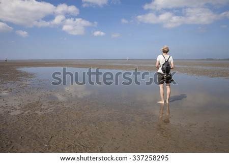 Germany, Lower Saxony, Low tide, woman standing on water's edge