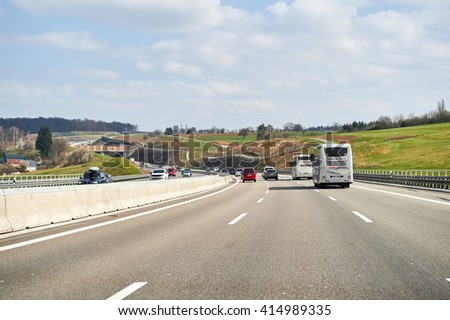 GERMANY - MAR 26, 2016: Bundesautobahn or Federal Motorway highway with busy traffic on a spring day with beautiful green fields and blue clouds - stock photo