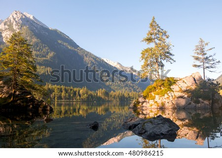 Germany. Mountain forest lake Hintersee. Water mirror, the cloudless sky and the dawn