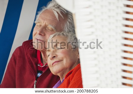 Germany, North Sea, St.Peter-Ording, Senior couple resting on hooded beach chair, close-up - stock photo