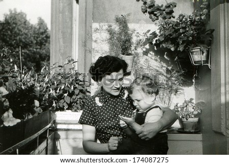 GERMANY -  1960s: An antique photo shows woman with a little boy in her arms sitting on the balcony