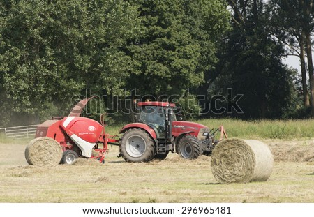 Germany - Schleswig Holstein, July 4, 2015: Hay with a round baler in a field in Schleswig Holstein in ferryman sand Wedel 2015