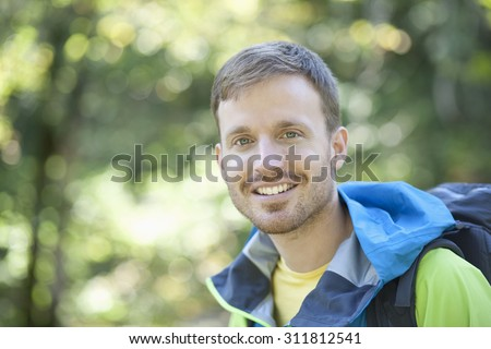 Germany,Upper Bavaria,Man with backpack,smiling,portrait