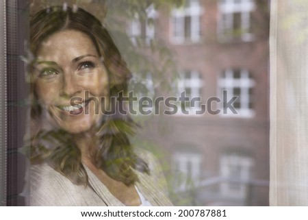 Germany, Woman looking out the window smiling - stock photo