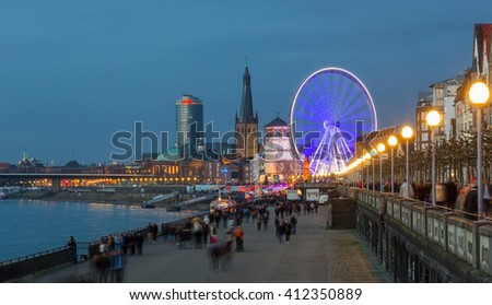 GERNANY, DUESSELDORF, 27 DECEMBER 2015: guests and residents of the city in the evening walk along the Rhine promenade.
