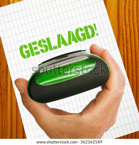 Geslaagd, passed in dutch language concept with rubber stamp in hand, paper and wooden table - stock photo