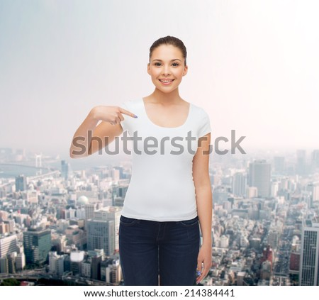 gesture, advertising and people concept - smiling young woman in blank white t-shirt pointing finger on herself over city background - stock photo