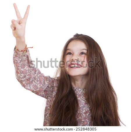Gesture and happy people concept - smiling little girl in dress showing peace gesture with fingers, studio on white background  - stock photo