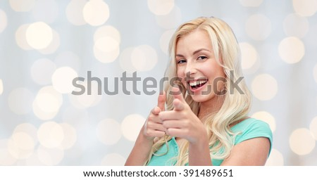 gesture and people concept - happy smiling young woman or teenage girl pointing finger to you over holidays lights background - stock photo
