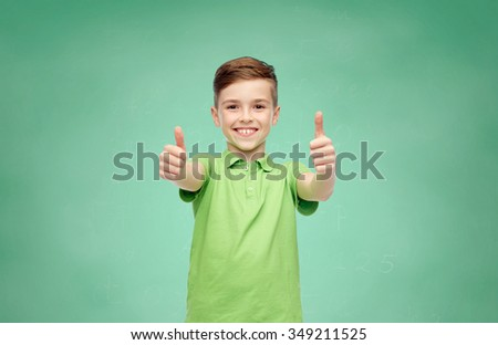gesture, childhood, fashion and people concept - happy smiling boy in green polo t-shirt showing thumbs up over green school chalk board background - stock photo