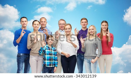 gesture, family, generation and people concept - group of smiling men, women and boy showing ok hand sign over blue sky and clouds background - stock photo