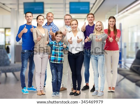gesture, family, travel, generation and people concept - group of smiling men and women showing thumbs up over airport waiting room background - stock photo
