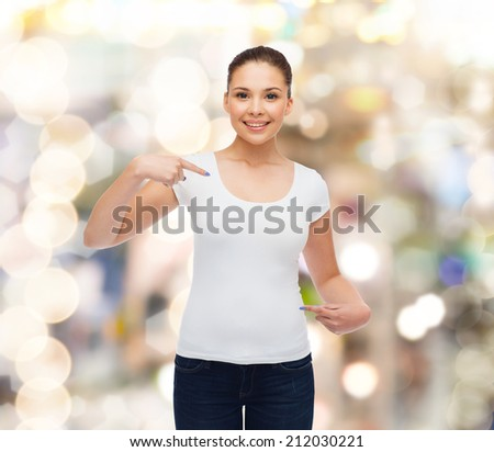 gesture, holidays, advertising and concept - smiling young woman in blank white t-shirt pointing fingers on herself over sparkling background - stock photo
