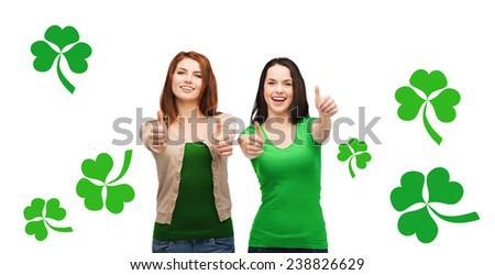 gesture, holidays, st. patricks day and happy people concept - two smiling girls showing thumbs up over white background with green shamrock or clover - stock photo