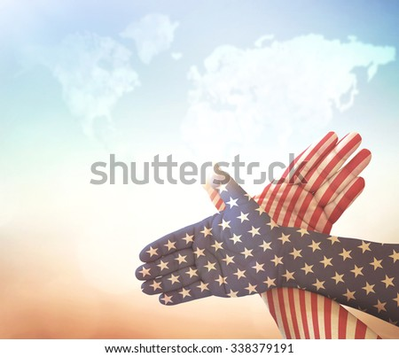 Gesture made by american flag colored hands showing symbol of eagle over blurred world map of clouds background. Concept for Independence Day and other events. - stock photo