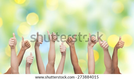 gesture, people, human race and international society concept - human hands showing thumbs up over green lights background - stock photo