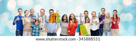 gesture, sale and people concept - group of smiling men, women and kids showing thumbs up and holding shopping bags with credit card over blue holidays lights background - stock photo