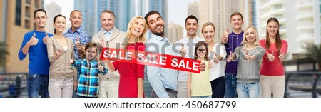 gesture, shopping and people concept - group of happy people with sale sign showing thumbs up