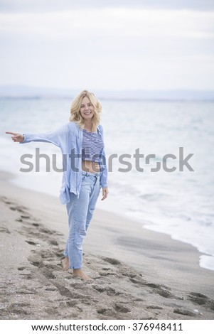 """gesture. The ease of mind. Woman enjoying the sea breeze , sea and sand . Smiles , do not think of """"tomorrow"""" . - stock photo"""