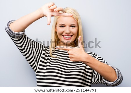 Gesturing finger frame. Beautiful young blond hair woman looking at camera and gesturing finger frame while standing against grey background  - stock photo