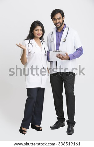 Gesturing two young Indian attractive doctors on white background. - stock photo