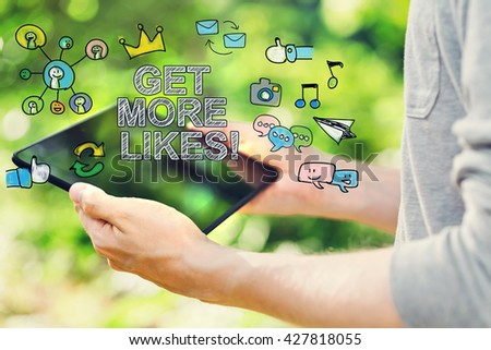 Get More Likes concept with young man holding his tablet computer outside in the park - stock photo