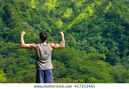 Get out get fit! Young male flexing outdoors.  - stock photo