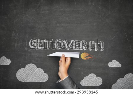 Get over it concept on black blackboard with businessman hand holding paper plane - stock photo